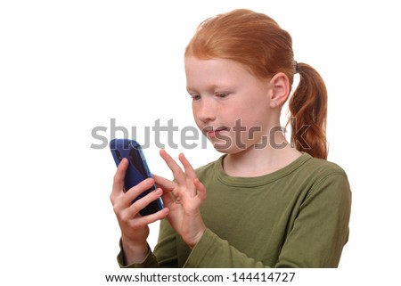Red haired girl plays with her new smartphone - stock photo