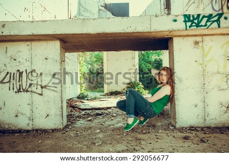 Red-haired girl walks along deserted unfinished buildings - stock photo