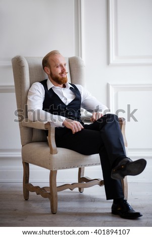 Red-haired man with a red beard in the classic black trousers, white shirt and a black vest sits on a chair and looking out the window - stock photo