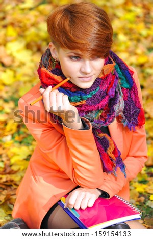 Red-haired student girl with notebook on a background autumn leaves - stock photo