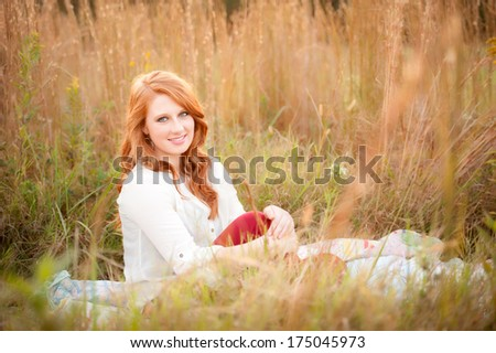red haired teen girl in a field  - stock photo