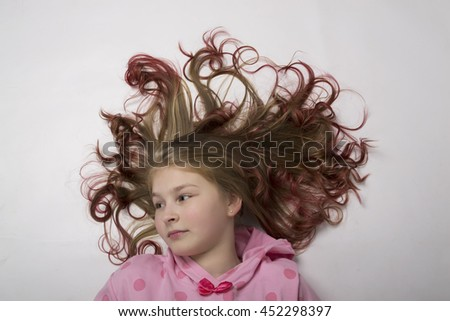 red-haired teenager girl lying on the floor with her hair form a circle - stock photo