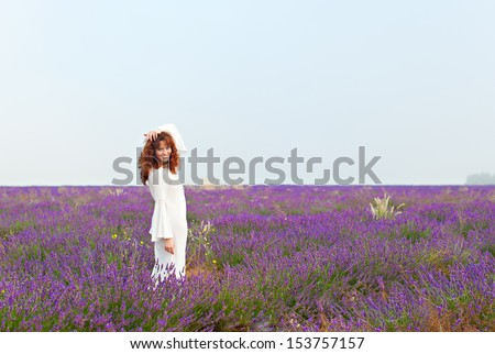 Red-haired white woman in a long white shirt on a lavender field, smiling, looking into the camera - stock photo