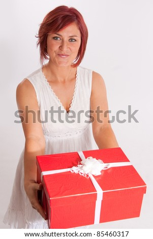 Red haired woman holding a red and white present - stock photo