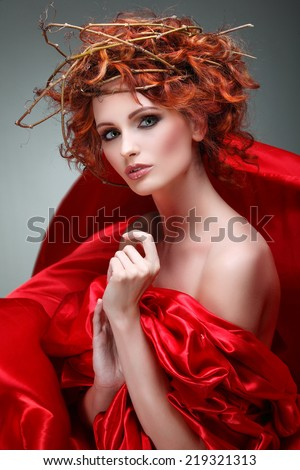 Red hairs. Portrait of beautiful girl in red fabric in a chaplet from branches. - stock photo