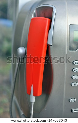 red handset of a public telephone - stock photo