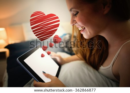 red heart against pretty redhead using tablet lying on her bed - stock photo