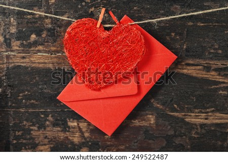 Red  heart and envelop  hanging on the clothesline. On old wood background - stock photo