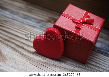 Red heart and small gift box with a bow on a wooden background. Greeting card for lovers, friendship or valentine's day. - stock photo