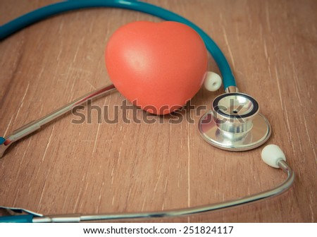Red heart and stethoscope on wooden background. - stock photo