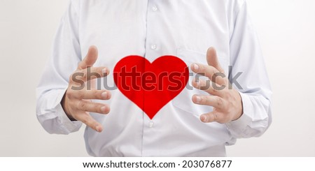 red heart between man's  hands on white shirt background close up shoot Idea protection diseases of  heart  - stock photo