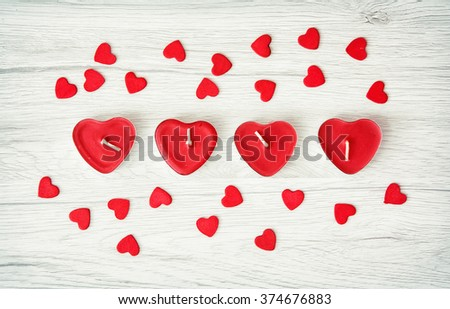 Red heart candles little decorative hearts on the wooden background. Valentine's Day. Symbol of love. - stock photo