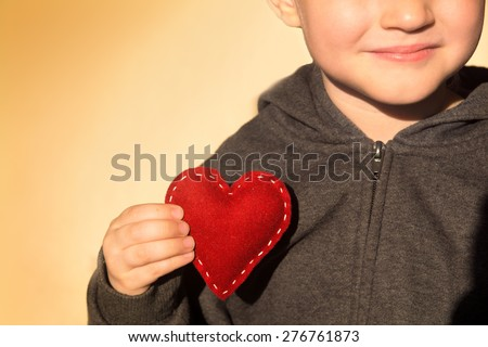 Red heart in child hands. Kindness concept, gift, hand made valentine, close up, horizontal, copy space - stock photo
