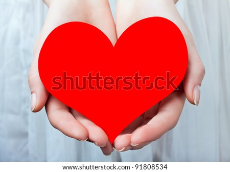 Red heart in her hands, on a light background - stock photo