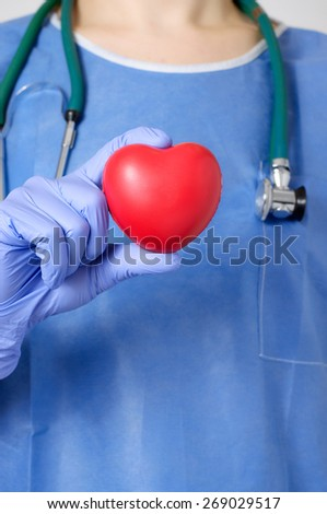 Red heart in the hand of a doctor - stock photo
