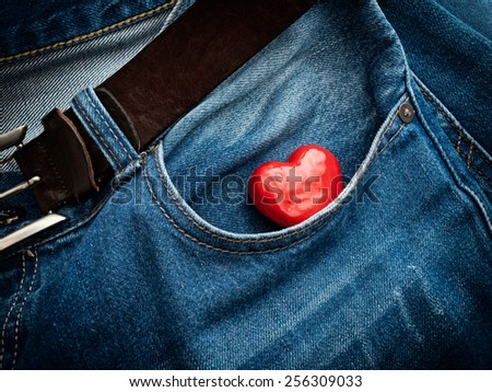 Red heart in the pocket of jeans trousers. - stock photo
