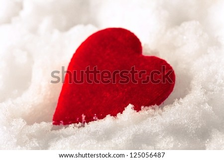 Red heart in the snow - stock photo
