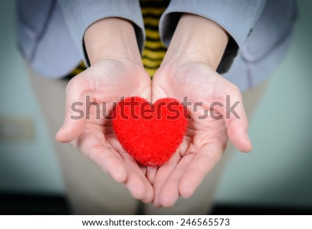 Red heart in woman hands - stock photo