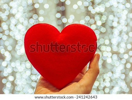 Red heart in woman hands, on light blue bokeh background - stock photo