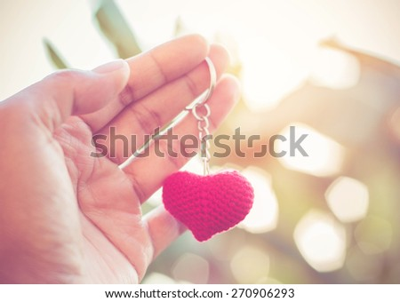 Red heart in woman hands with sunset light background. - stock photo
