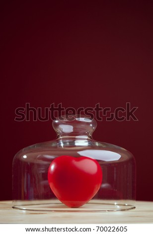 Red heart inside a glass dome (selective focus) - stock photo