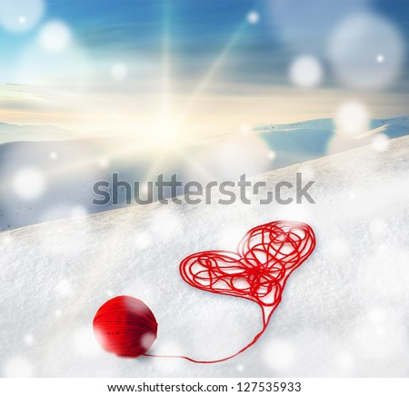 Red heart made of wool thread on snow in winter mountains landscape in rays of sun light. Valentine day greeting, card, illustration, poster - stock photo