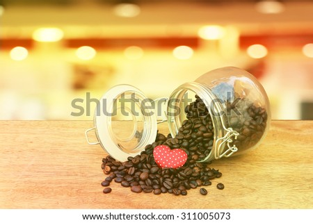 red heart on coffee seed pouring from glass pot with blur light in restaurant background - stock photo
