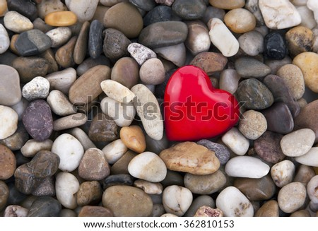 Red heart on pebbles background - stock photo