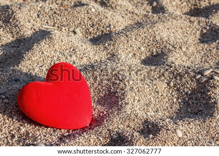 Red heart on the beach with small pebbles  background. - stock photo
