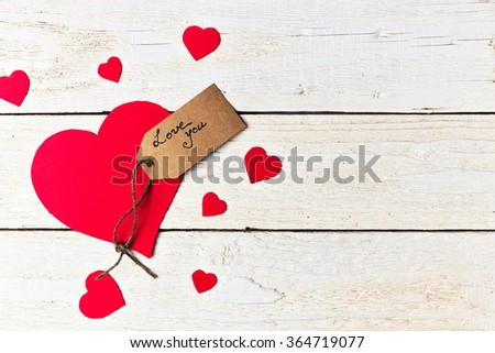 Red heart paper cut with craft label on white wooden background. Valentines day. - stock photo