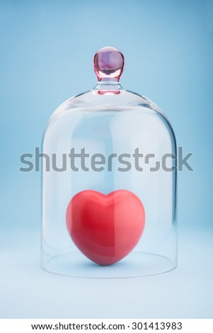 Red heart protected under a glass dome on blue background - stock photo
