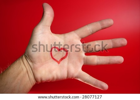 Red heart shape drawn on a male human hand, red background - stock photo