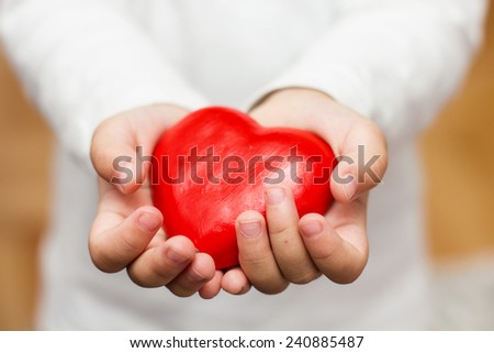 Red Heart Shape In Child Hands. - stock photo