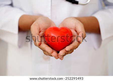 Red heart shape in doctor's hands - stock photo