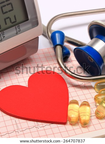 Red heart shape on electrocardiogram graph, medical stethoscope, instrument for measuring blood pressure and tablets, ekg heart rhythm, medicine concept - stock photo