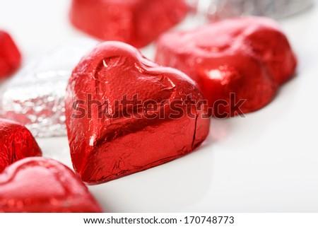 Red heart shaped chocolates on white background - stock photo