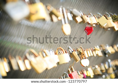 Red heart shaped lock on a bridge in Paris - stock photo