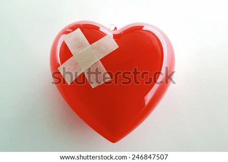 Red heart with adhesive plaster isolated on white background - stock photo