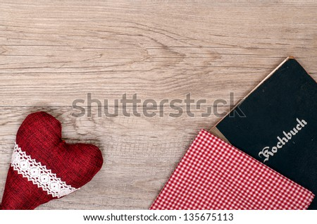 Red heart with checkered cloth and book on old wood - stock photo