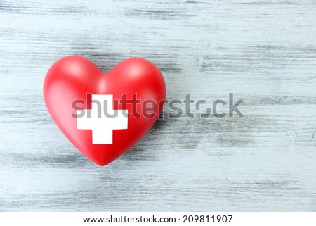 Red heart with cross sign on color wooden background - stock photo