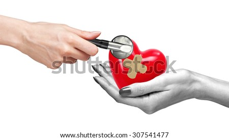 Red heart with medical path in woman hand and stethoscope isolated on white - stock photo