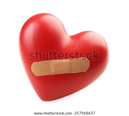 Red heart with plaster isolated on white - stock photo