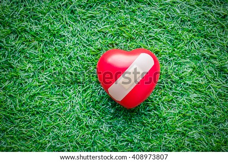 Red heart with plaster on grass - stock photo