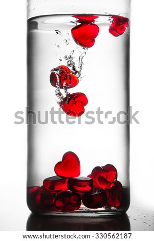 Red hearts falling in glass of water - stock photo