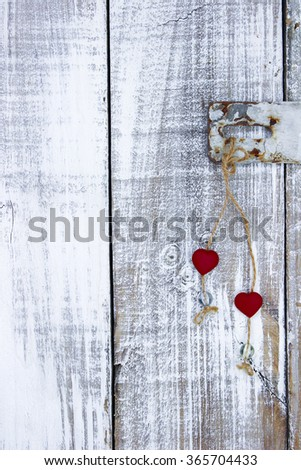 Red hearts hanging from rope on latch of white painted rustic antique wood door latch; Valentine's Day and love concept - stock photo
