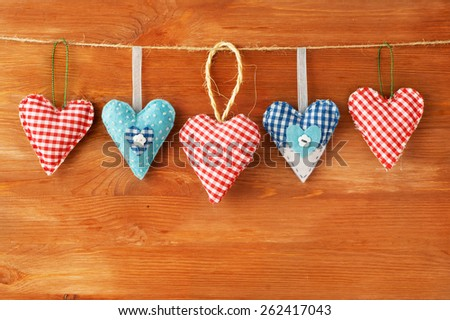 Red hearts hanging over grey wood background - stock photo