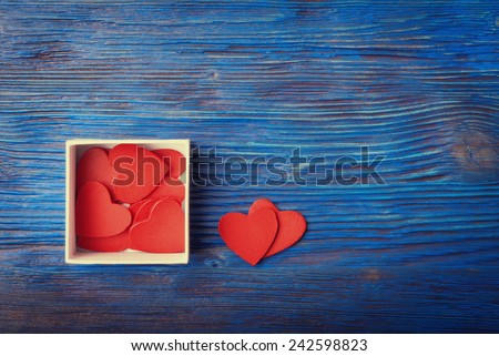Red hearts in box on old wooden blue background - stock photo