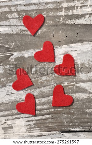 red hearts in felt on old  whitened  wooden background  - stock photo