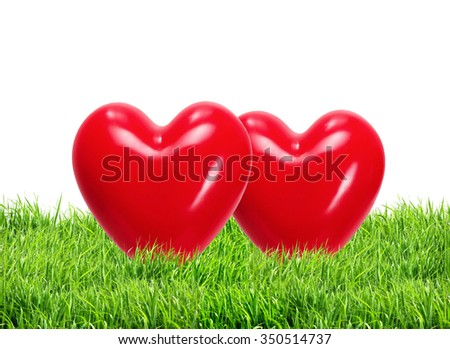 Red hearts in green grass over white background - stock photo