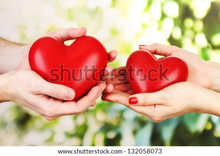 Red hearts in woman and man hands, on green background - stock photo